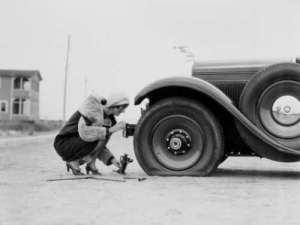 Woman-Changing-Flat-Tire-On-a-Car-Vintage-Photo
